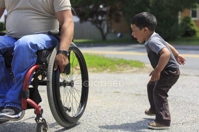 Латиноамериканець з Спінальним Кордом Інжюрі в інвалідному візку грає зі своїм сином — стокове фото
