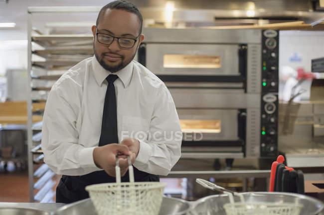 Afro-Américain avec le syndrome de Down comme chef cuisinier dans la cuisine commerciale — Photo de stock