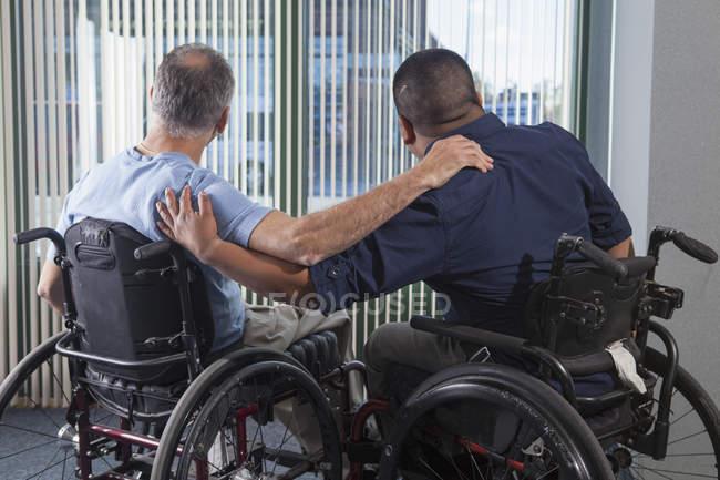 Двоє чоловіків з травмами спинного мозку на інвалідних візках дивляться через вікно офісу з руками навколо — стокове фото