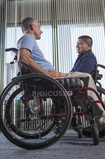 Двоє чоловіків з травмами спинного мозку на інвалідних візках розмовляють в офісному коридорі. — стокове фото