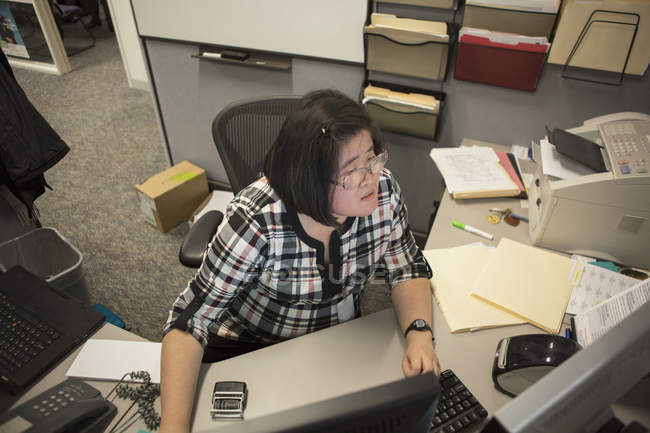Asian woman with a Learning Disability working at her computer in office — Stock Photo