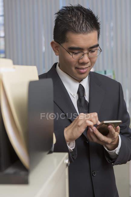 Азіатський чоловік з аутизмом, що працюють в офісі зі смартфоном — стокове фото