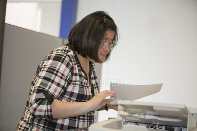 Mulher asiática com deficiência de aprendizagem trabalhando em uma máquina de cópia no escritório — Fotografia de Stock