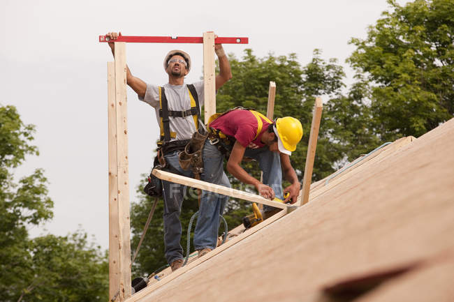 Hispanic carpenters leveling boards on roof of an under construction house — Stock Photo