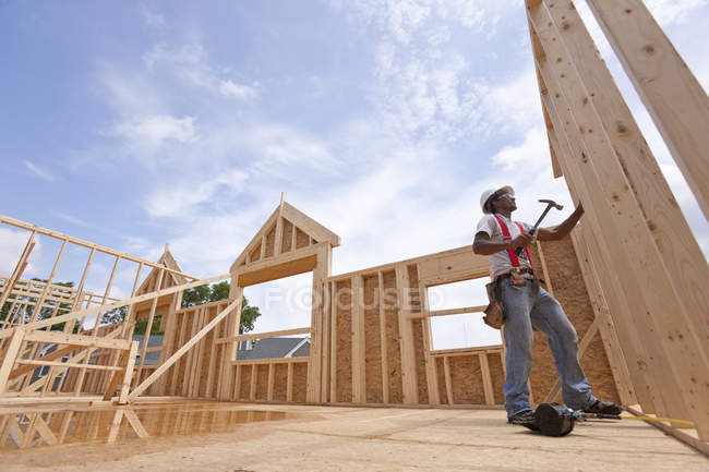 Hispanic carpenter working on the upper floor of a house under construction — Stock Photo
