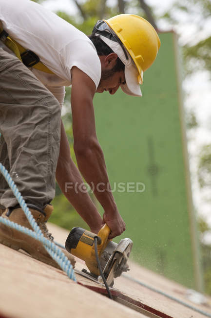 Hispanic carpenter using a circular saw on roof panel at a house under construction — Stock Photo
