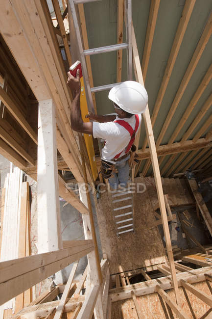 Hispanic carpenter carrying a level up ladder to second floor at a house under construction — Stock Photo