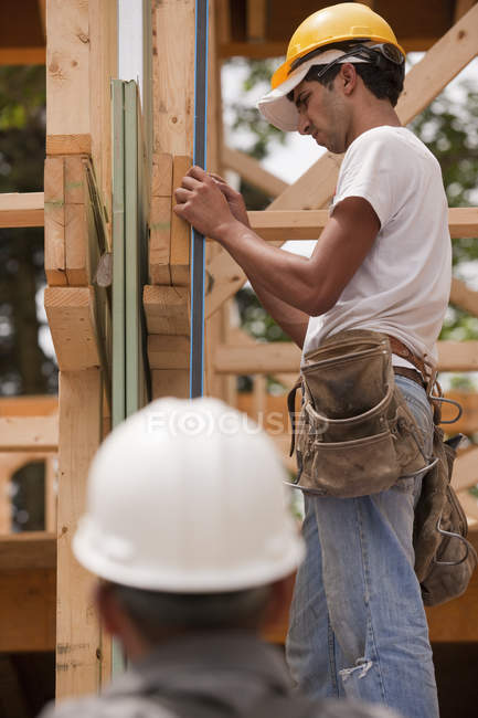 Hispanic carpenters measuring a frame with a level at a house under construction — Stock Photo