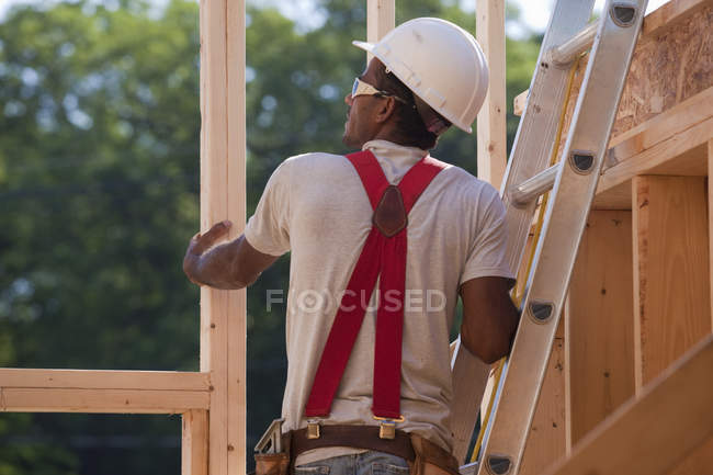 Hispanic carpenter on a ladder checking the framing of a house under construction — Stock Photo