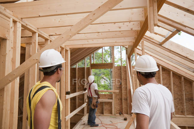 Hispanic carpenters studying their work on framing at a house under construction — Stock Photo