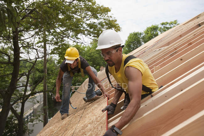 Hispanic carpenters placing roof panel at a house under construction — Stock Photo