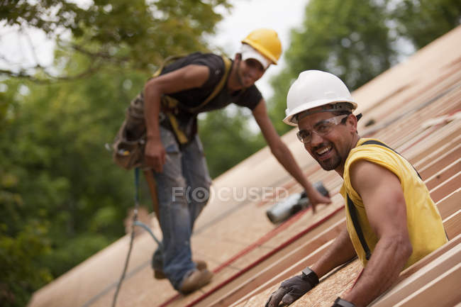 Carpenters working on the roof of a house under construction — Stock Photo