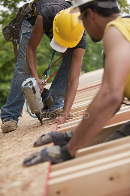 Hispanic carpenters placing roof panel with a nail gun at a house under construction — Stock Photo