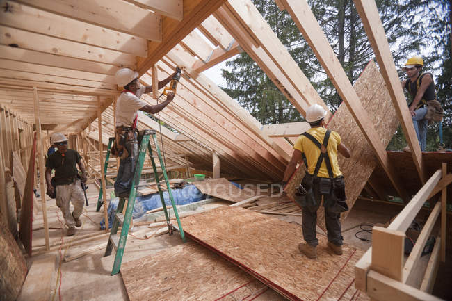 Hispanic carpenters installing roof panel through upper floor at a house under construction — Stock Photo