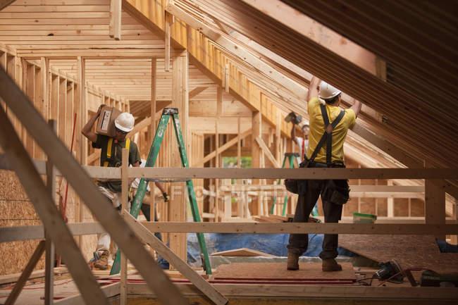 Латиноамериканські теслі приносили на дах будинок під час будівництва. — стокове фото