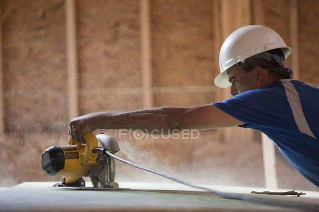 Hispanic carpenter using a circular saw on the roofing sheathing at a house under construction — Stock Photo