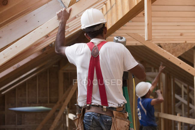 Hispanic carpenter using nail gun on upper floor at a house under construction — Stock Photo