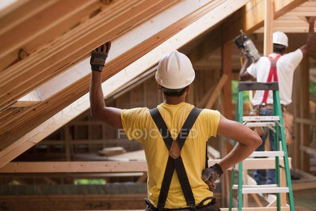 Латиноамериканські теслі працюють на балках даху в будинку під час будівництва. — стокове фото