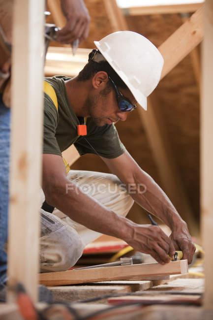 Charpentier hispanique marquant une mesure sur une planche dans une maison en construction — Photo de stock