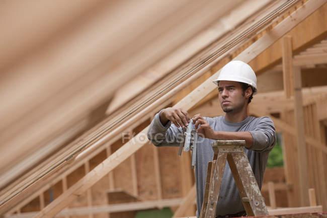 Латиноамериканський тесляр стоїть на драбині, тримаючи металеве підкріплення, і чіпляється за будинок під час будівництва. — стокове фото