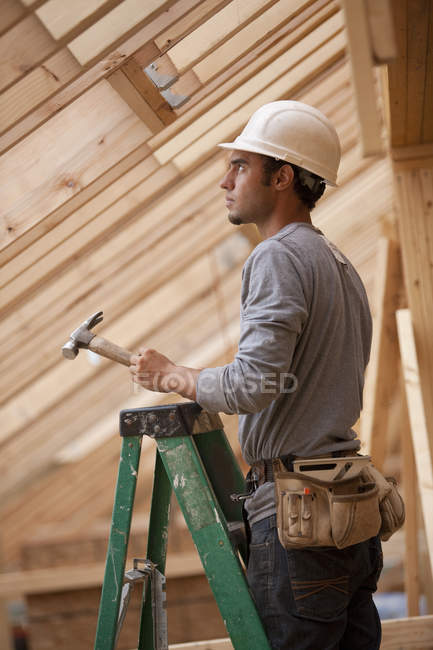 Hispanic carpenter standing on a ladder with a hammer at a house under construction — Stock Photo