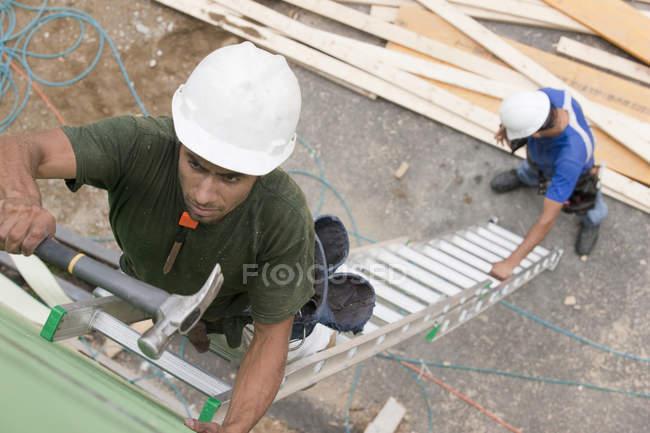 Карпати на розширеній драбині для встановлення оббивки на будівельному майданчику. — стокове фото