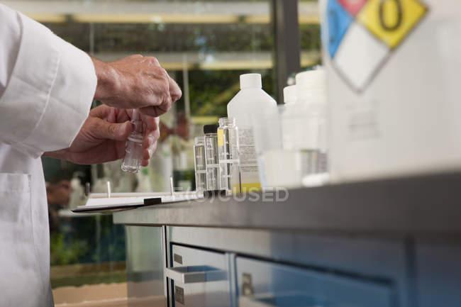 Image recadrée du scientifique travaillant avec des bouteilles d'échantillon dans le laboratoire de l'usine de traitement de l'eau — Photo de stock