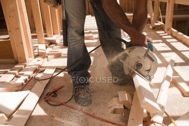 Charpentier hispanique utilisant une scie circulaire à bord sur un chantier de construction — Photo de stock