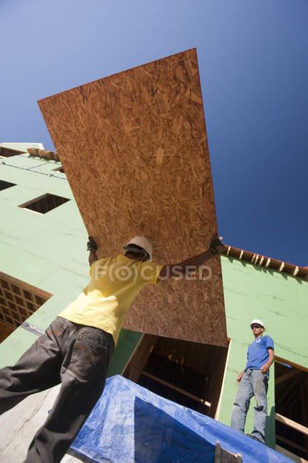 Falegnami ispanici che trasportano guaine in una casa in costruzione — Foto stock
