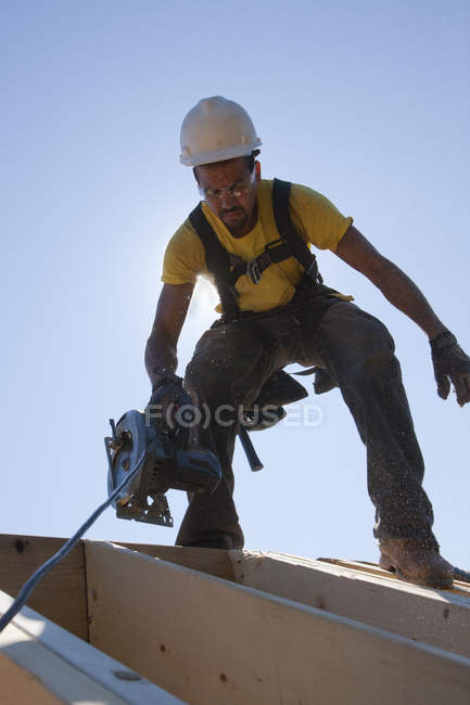 Латиноамериканське тесляр з круглою пилою на балках даху в будинку під час будівництва. — стокове фото