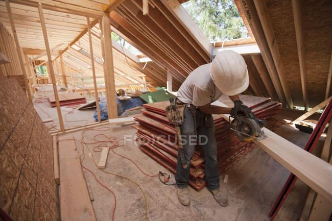 Menuisier à l'aide d'une scie circulaire sur le bûcher du toit dans une maison en construction — Photo de stock