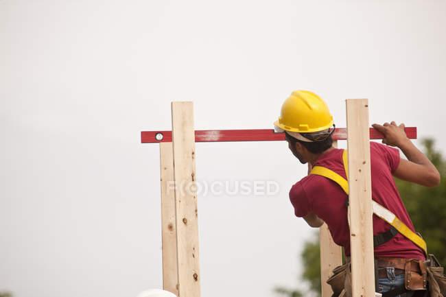 Falegname ispanico che misura i camini con un livello in una casa in costruzione — Foto stock