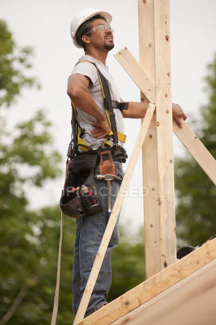 Falegname ispanico che esamina i camini di una casa in costruzione — Foto stock