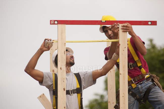 Falegnami di misurazione e livellamento camino pila in una casa in costruzione — Foto stock