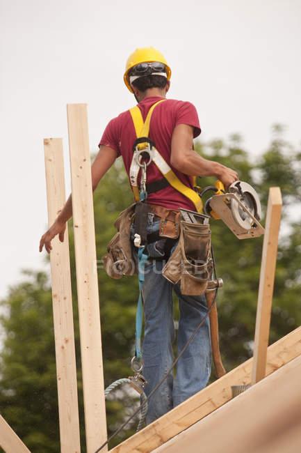 Charpentier hispanique utilisant une scie circulaire sur le toit d'une maison en construction — Photo de stock