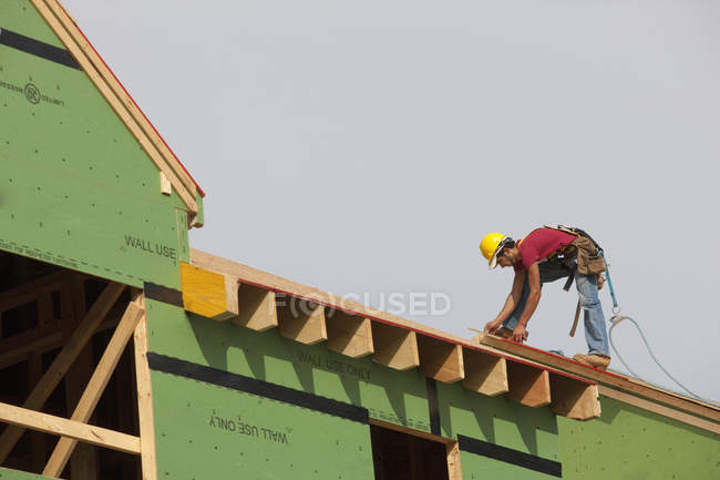 Hispanic carpenter measuring a roof panel of a house under construction — Stock Photo