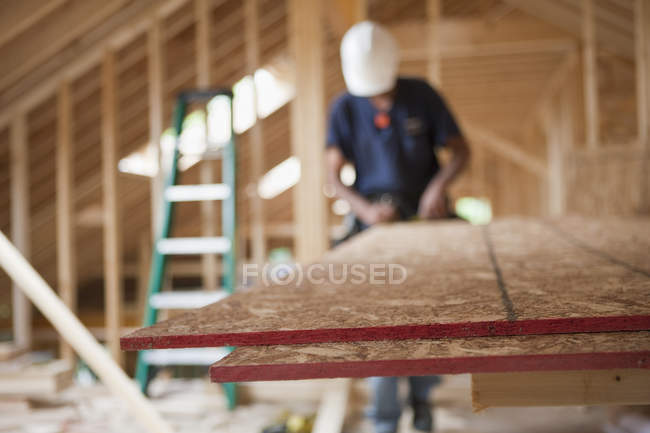Carpenter using a circular saw on particle board in a house under construction — Stock Photo