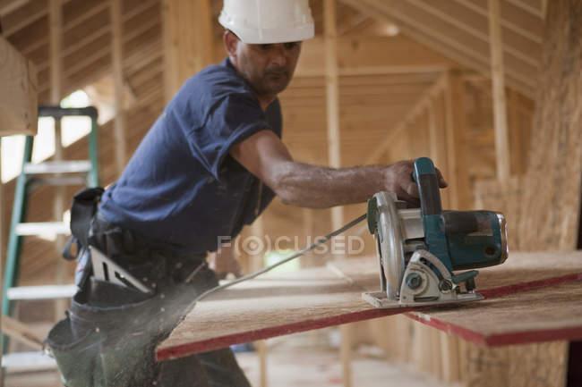 Panneau de toit de taille de charpentier hispanique avec une scie circulaire dans une maison en construction — Photo de stock