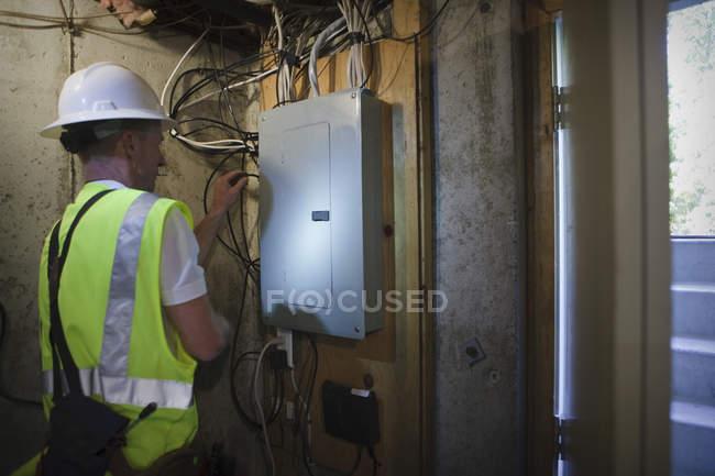 Câble installateur travaillant au panneau d'alimentation dans la cave d'une maison — Photo de stock