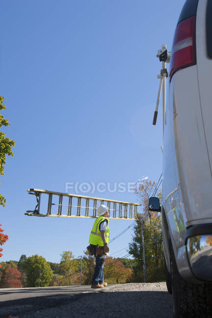 Engineer carrying a ladder to climb power pole — Stock Photo