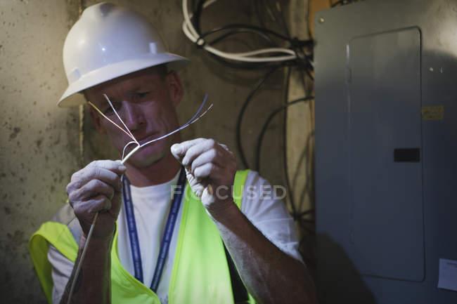 Kabelinstallateur bereitet sich darauf vor, Kabel an Stromverteiler im Keller eines Hauses zu kleben — Stockfoto