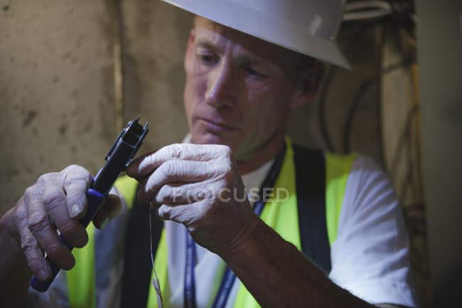 Câble installateur mettant connecteur sur un fil dans la cave d'une maison — Photo de stock