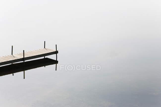 Vue grand angle de jetée vide dans un lac gris calme — Photo de stock