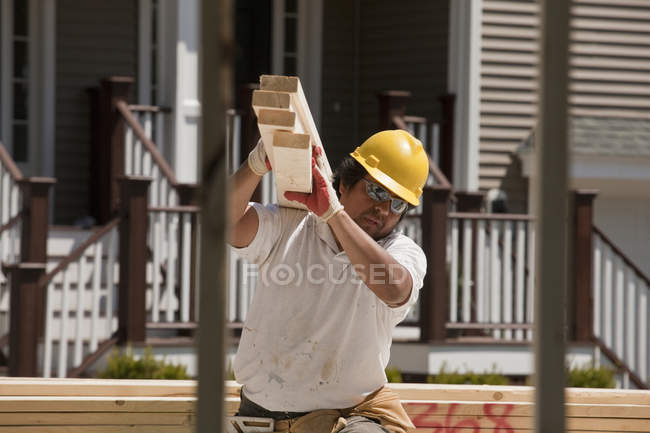 Carpenter carrying planks at a construction site — Stock Photo