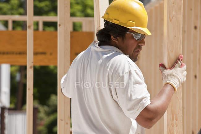Плотник поднимает деревянную раму на строительной площадке — стоковое фото