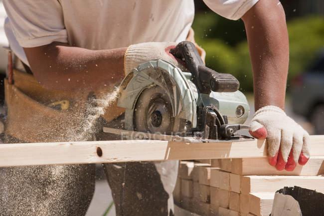 Charpentier sciant des montants muraux sur un chantier de construction — Photo de stock