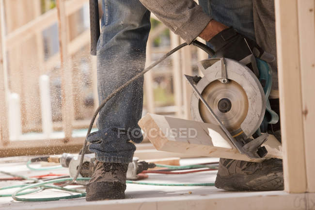 Carpenter sawing a plank at a construction site — Stock Photo