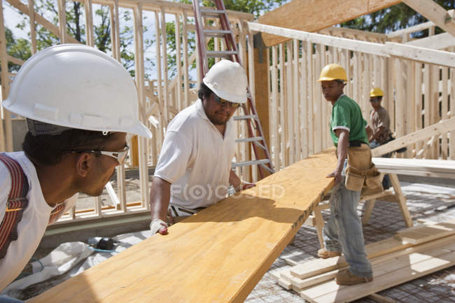 Carpenters lifting a laminated beam at a construction site — Stock Photo