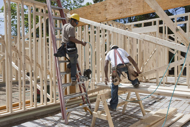 Carpenters framing a house at a building construction site — Stock Photo