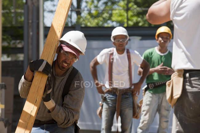 Колектори піднімають балку на будівельному майданчику. — стокове фото